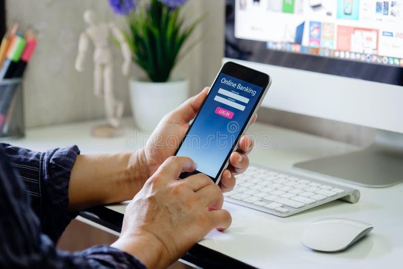 Homme avec le téléphone en ligne d'application de banque à l'espace de travail de bureau dans le bureau images libres de droits