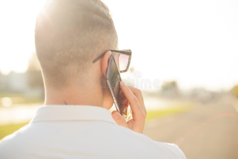 Homme avec le téléphone portable dans des mains, vue arrière, extérieure images libres de droits