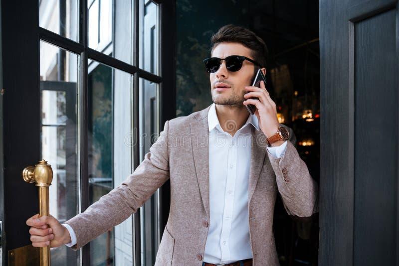 Homme avec le téléphone portable marchant du café images stock