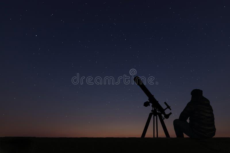 Homme avec le télescope d'astronomie regardant les étoiles photo stock