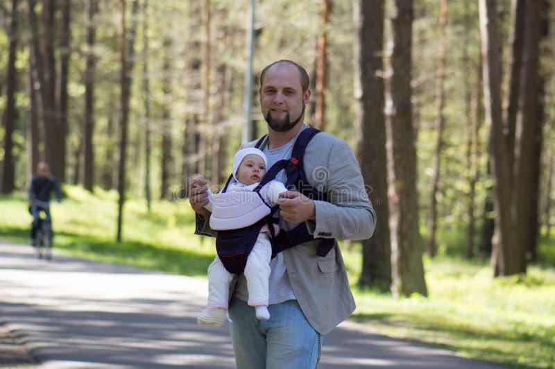 Homme avec le transporteur de bébé images stock