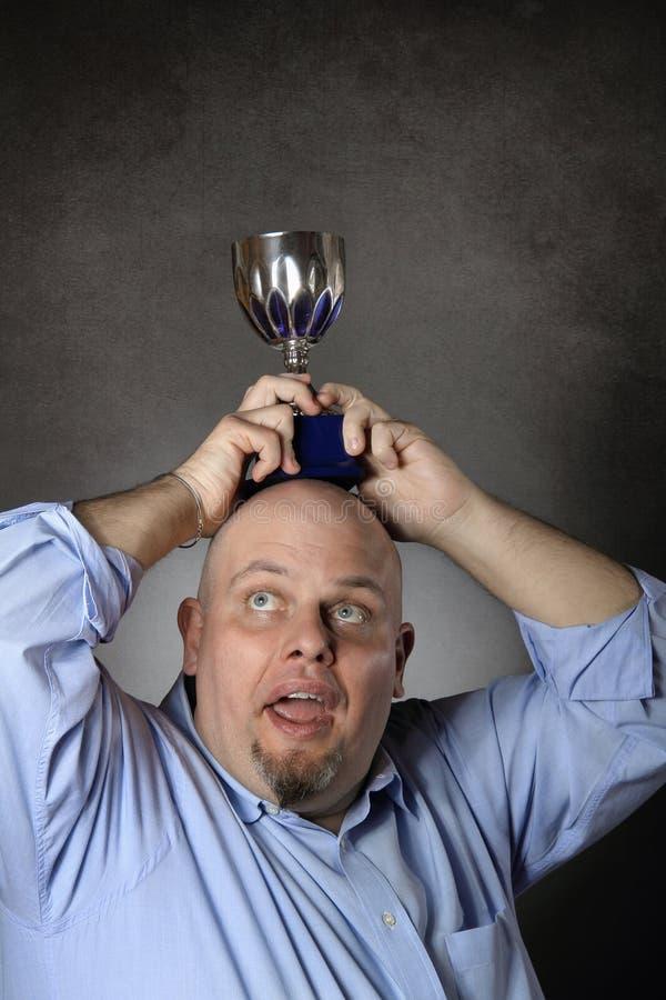 Homme avec le trophée de gain au-dessus de sa tête photographie stock libre de droits