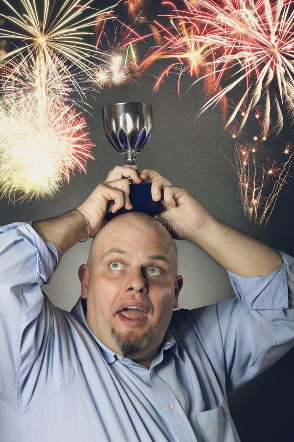 Homme avec le trophée de gain au-dessus de sa tête et feux d'artifice photo libre de droits