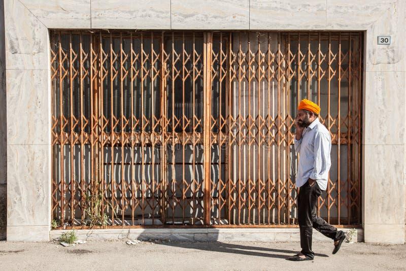 Homme avec le turban orange devant la boutique à volets photo libre de droits
