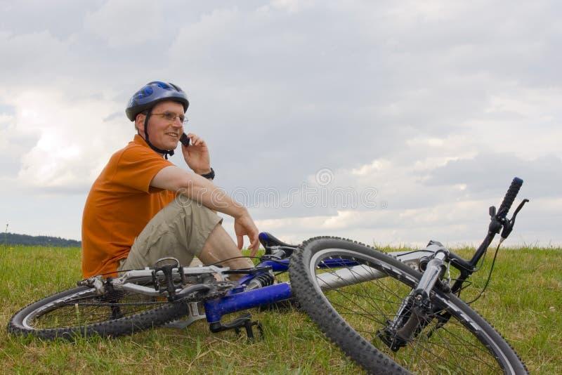 Homme avec le vélo de montagne parlant sur le téléphone portable image libre de droits