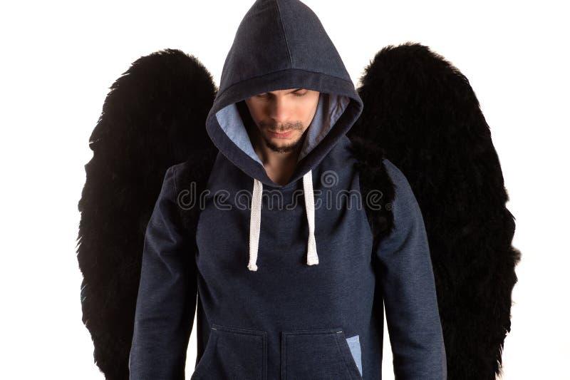 Homme avec les ailes noires dans la veste grise avec le capot jeté au-dessus de sa position et regards de tête vers le bas image stock