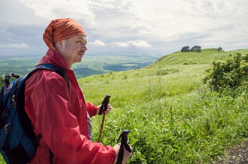 Homme avec les bâtons pour la marche nordique et la veste rouge avec la marche et le trekking de sac à dos dans les montagnes image stock