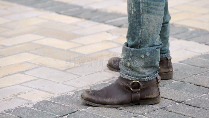 Homme avec les bottes brunes et les jeans déchirés se tenant à côté de la moto, motard dur images libres de droits