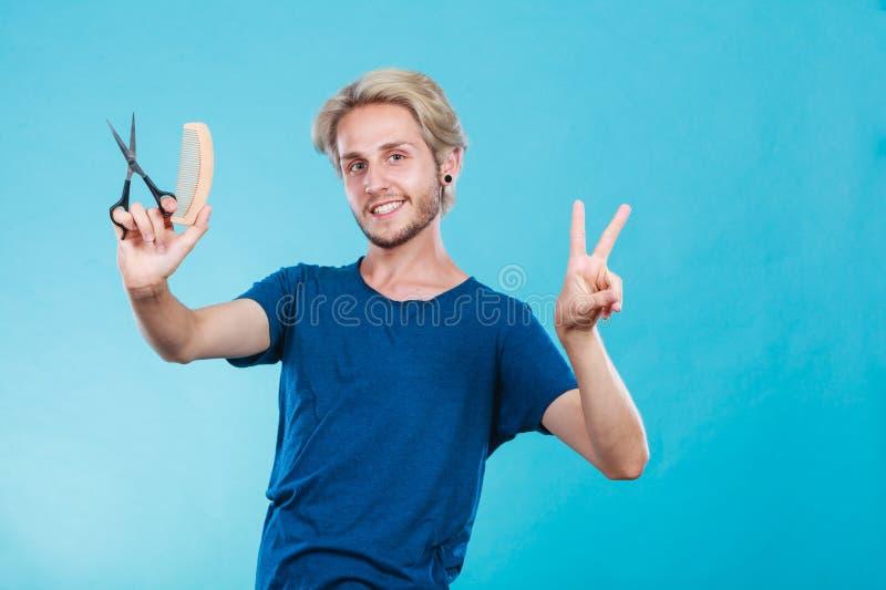 Homme avec les ciseaux et le peigne photographie stock libre de droits