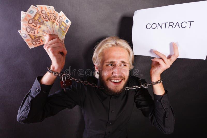 Homme avec les mains enchaînées tenant le contrat et l'argent photographie stock libre de droits