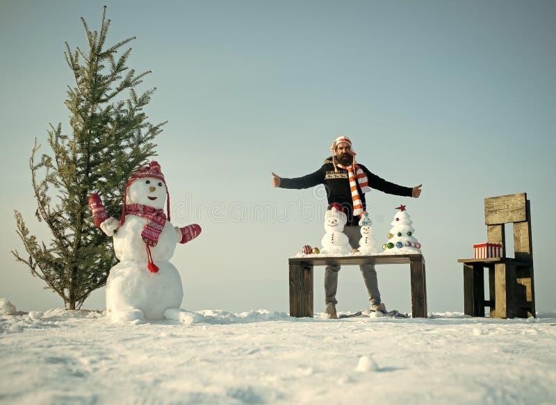 Homme avec les sculptures et les présents neigeux sur la table et la chaise photos stock
