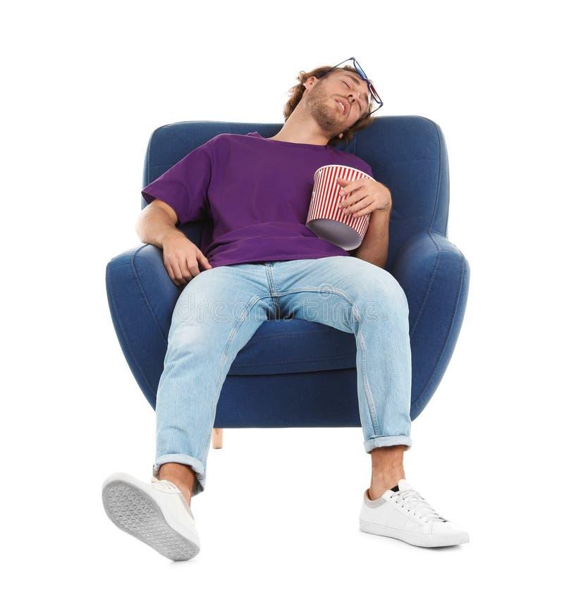 Homme avec les verres 3D et le maïs éclaté dormant dans le fauteuil pendant l'exposition de cinéma photos stock