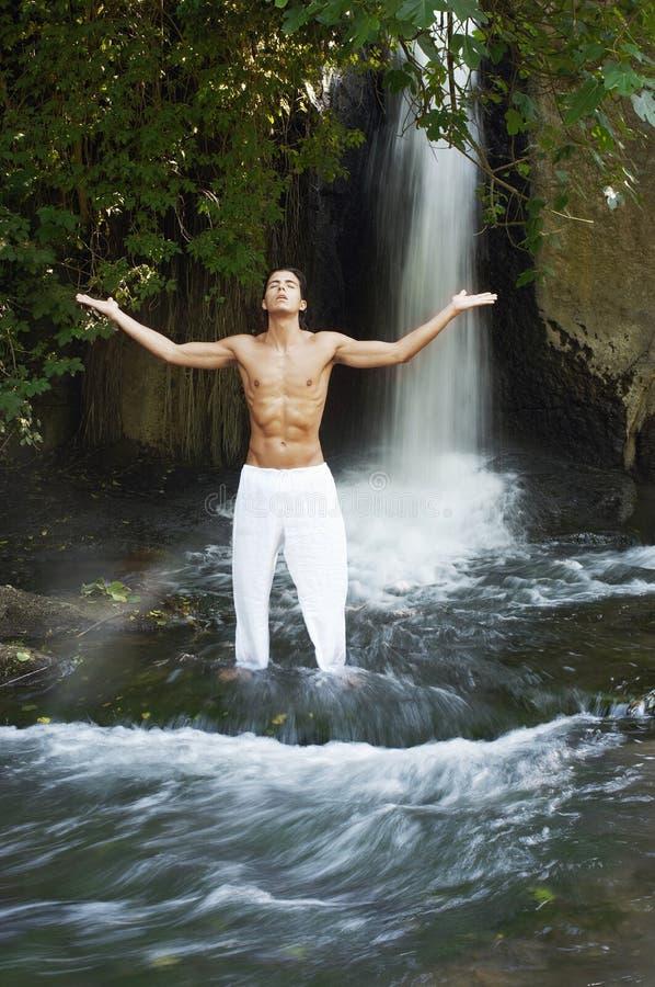 Homme avec méditer tendu par bras contre la cascade photos stock