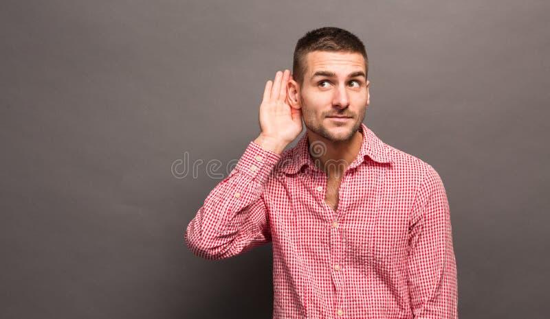 Homme avec sa main à l'oreille images stock