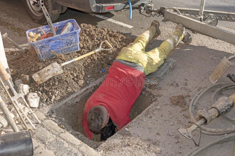 Homme avec sa tête en bas d'un trou dans la route photo stock