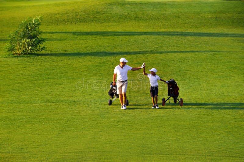 Homme avec ses golfeurs de fils marchant sur le terrain de golf photos libres de droits
