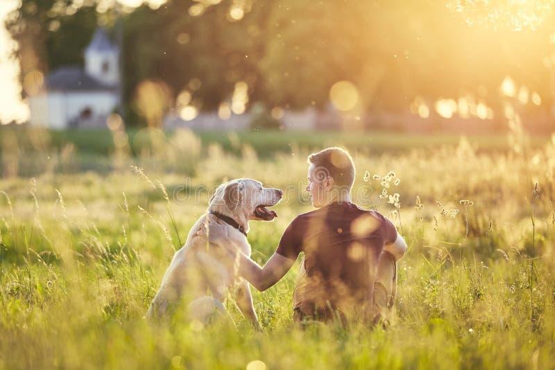 Homme avec son chien au coucher du soleil photo stock