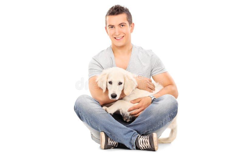 Homme avec son chien de bébé posé sur le plancher photographie stock