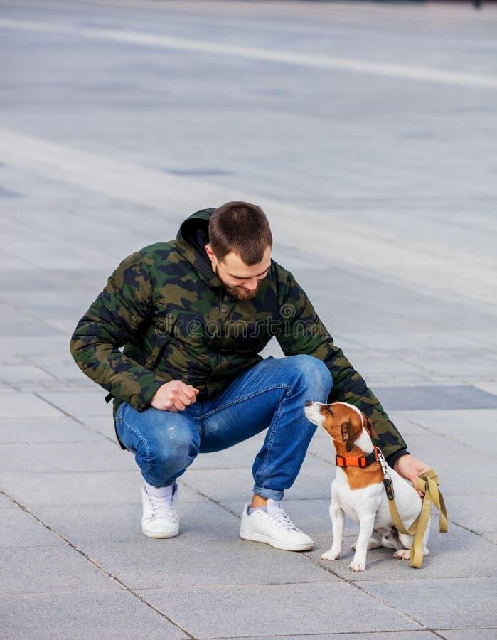 Homme avec son chien, Jack Russell Terrier, sur la rue de ville image stock