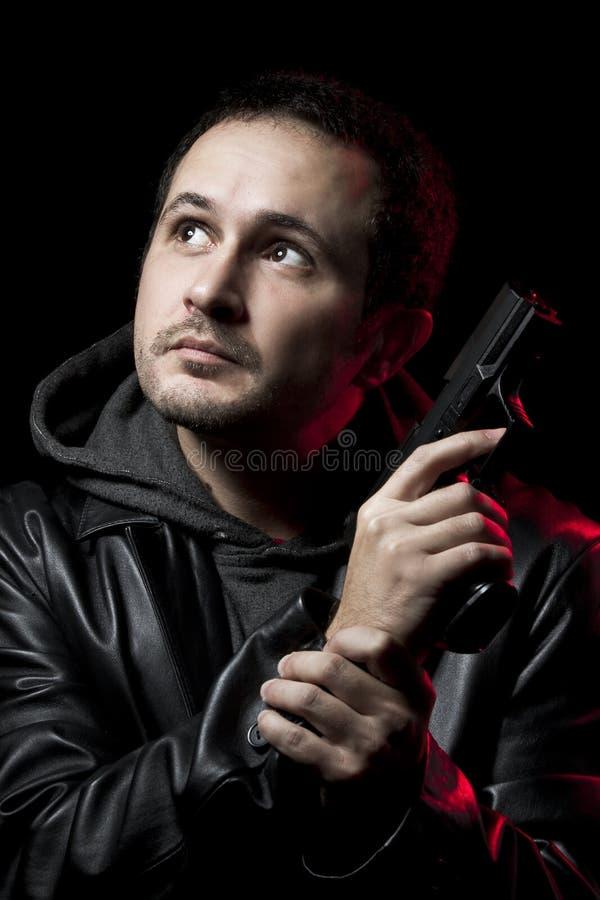 Homme avec un canon et rectifié en cuir noir photographie stock libre de droits