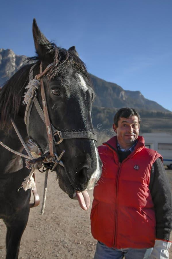 Homme avec un cheval noir photo stock
