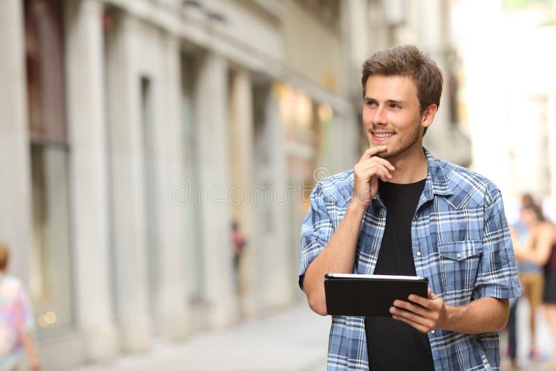 Homme avec un comprimé pensant dans la rue photos stock