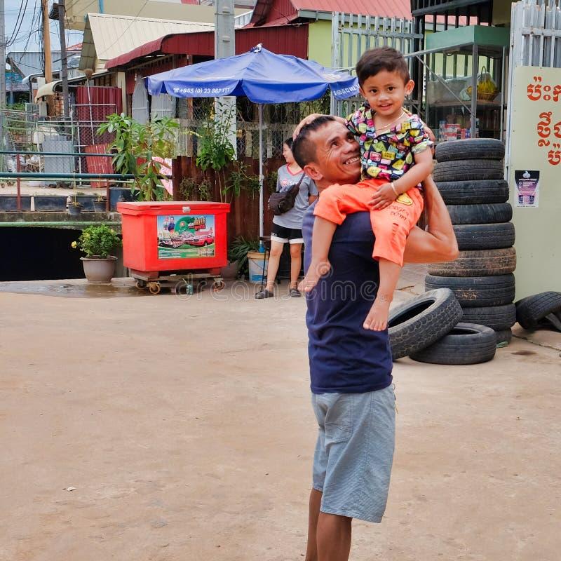 Homme avec un enfant dans des ses bras près du magasin de pneu, taudis de l'Asie, résidents des secteurs pauvres de photographie stock libre de droits