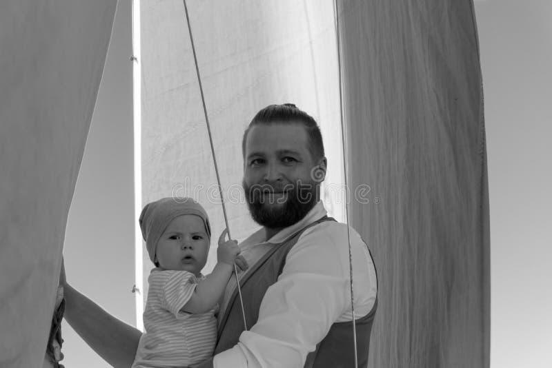 Homme avec un enfant sur un bateau de navigation images libres de droits
