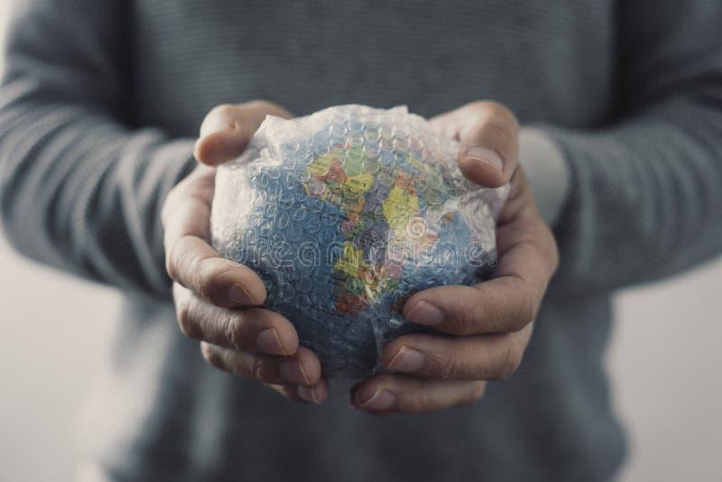 Homme avec un globe du monde enveloppé dans l'enveloppe de bulle photographie stock
