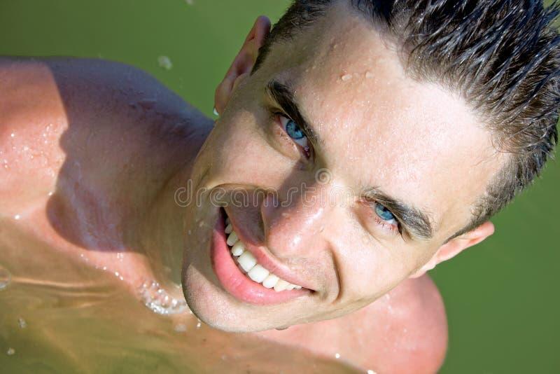 Homme avec un grand sourire dans l'eau photographie stock