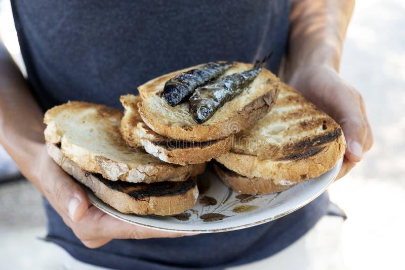 Homme avec un plat de pain et des sardines photos stock