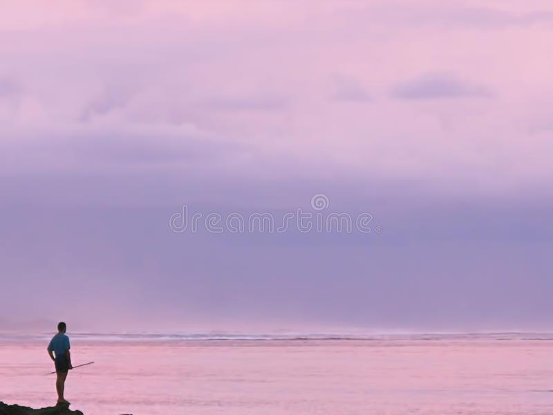 Homme avec une canne à pêche devant un coucher du soleil rose avec des vagues de mer photo libre de droits
