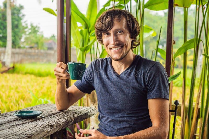 Homme avec une tasse de café sur la véranda de café près des terrasses de riz sur Bali, Indonésie photos stock