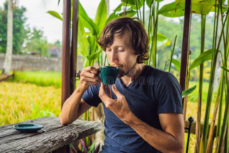Homme avec une tasse de café sur la véranda de café près des terrasses de riz sur Bali, Indonésie images stock
