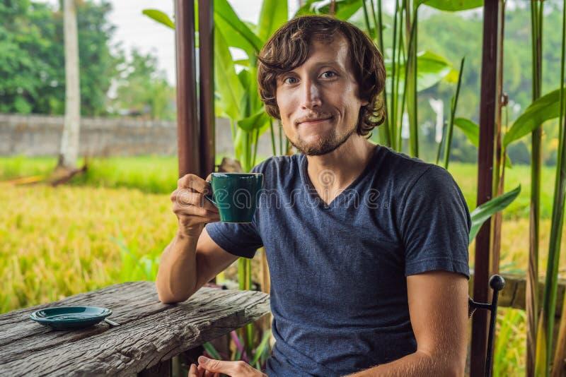 Homme avec une tasse de café sur la véranda de café près des terrasses de riz sur Bali, Indonésie photos libres de droits