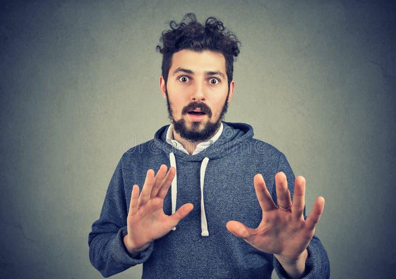 Homme ayant la phobie et la défendant avec des mains images stock