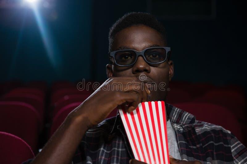 Homme ayant le maïs éclaté tout en observant le film photographie stock libre de droits