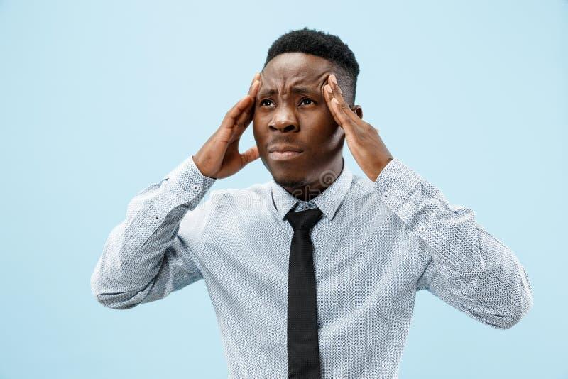 Homme ayant le mal de tête D'isolement au-dessus du fond bleu photographie stock libre de droits