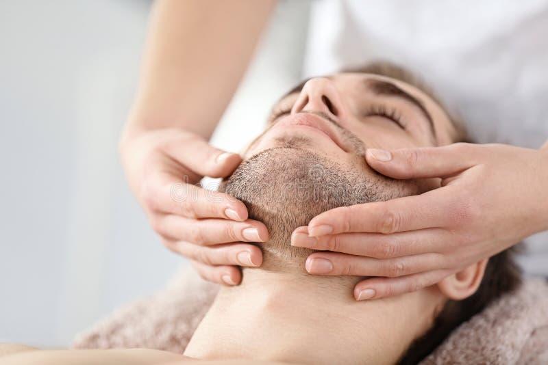 Homme ayant le massage de visage dans le salon photo stock
