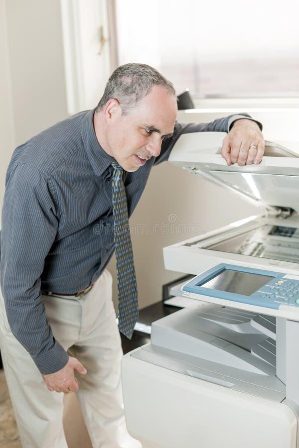 Homme ayant le problème avec le photocopieur dans le bureau photographie stock libre de droits
