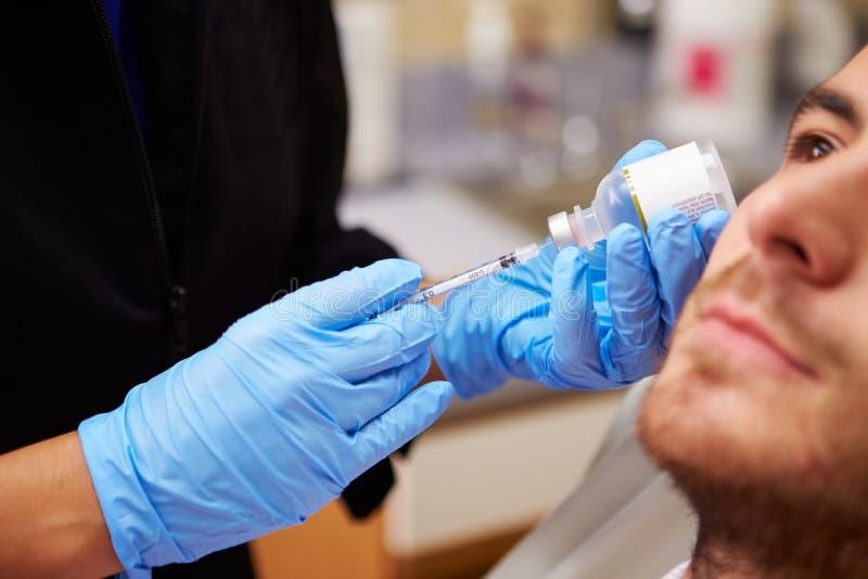 Homme ayant le traitement de Botox à la clinique de beauté image libre de droits