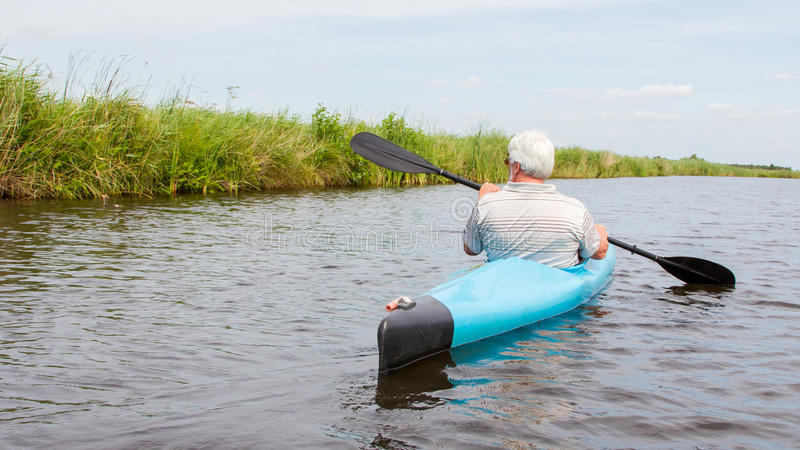 Homme barbotant dans un kayak bleu photographie stock libre de droits