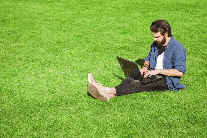 Homme barbu à l'aide de l'ordinateur portable images stock
