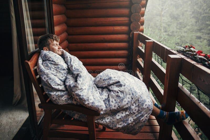 Homme barbu élégant détendant sur le porche en bois parmi la forêt dans le rai photographie stock
