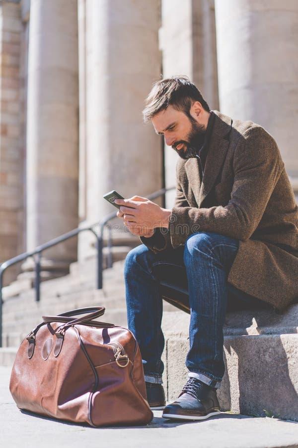 Homme barbu adulte à l'aide du smartphone dehors Message textuel professionnel occasionnel d'entrepreneur sur le smartphone en de image libre de droits