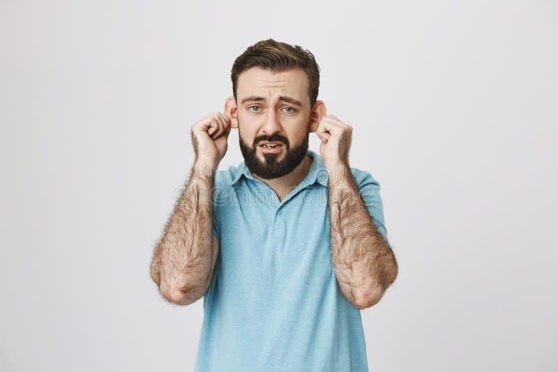 Homme barbu adulte avec le sourire sombre étirant des oreilles, imitant le singe triste, au-dessus du fond gris Le type est fatig photographie stock libre de droits