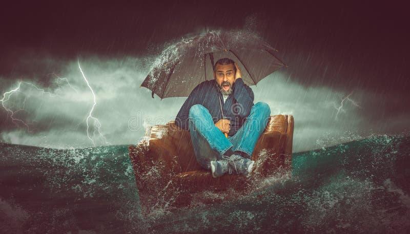 Homme barbu assis sur un fauteuil au milieu de la mer image libre de droits