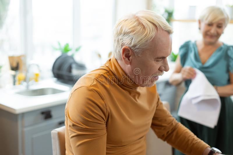 Homme barbu aux cheveux gris attirant bel élégant s'asseyant à la cuisine photographie stock libre de droits