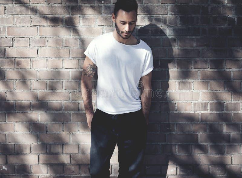 Homme barbu avec le tatouage utilisant le T-shirt blanc vide et les jeans noirs Fond de mur de briques Maquette horizontale, moll photo libre de droits