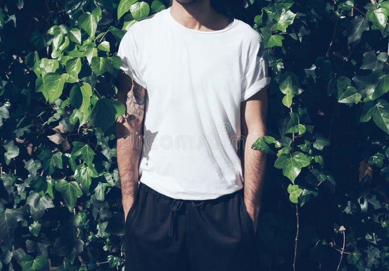 Homme barbu avec le tatouage utilisant le T-shirt blanc vide Fond vert de mur de jardin maquette horizontale images stock